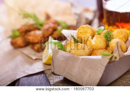 Beer snacks. Fried fried fish and cheese balls with lemon and greens. Snacks to different beers.