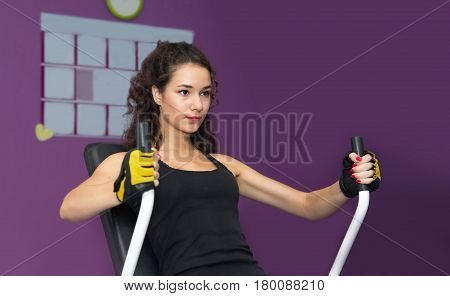 Girl training on simulator in gym. Young woman on Power trainers bench press chest exercise. Sport fitness flexing muscles on gym machine.