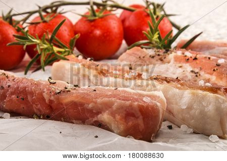 raw pork belly stripes with crushed peppercorn coarse salt rosemary and fresh tomato on white kitchen paper