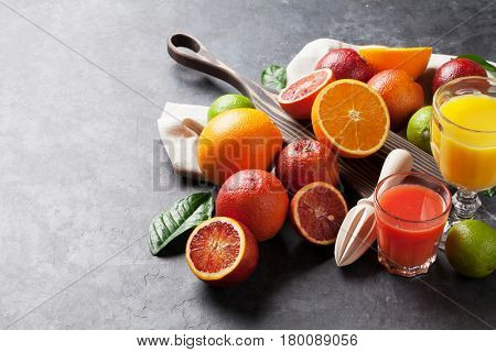 Fresh citruses and juice on dark stone background. Oranges and limes. View with copy space