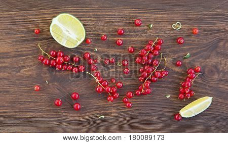 Fresh redcurrant. Ripe summer berries and lime on wooden background. Top view with copy space. Food background