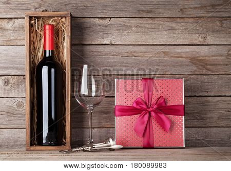 Red wine bottle, gift box and wine glass in front of wooden wall. With copy space