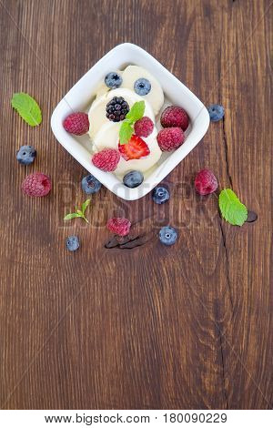 Milk fruit dessert. Whipped cream with berries. Serving tasty treats from dairy cream different berries and mint on the wooden table. White cup with cream berries and mint.