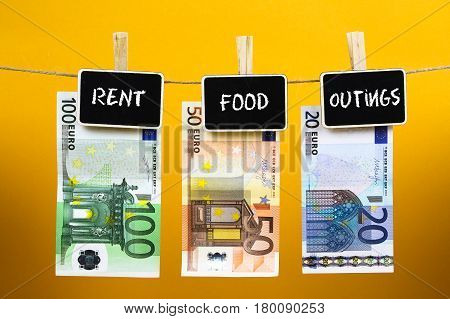 Bank Notes Suspended With Pins With Words - Rent Food Outings - Written On A Slate