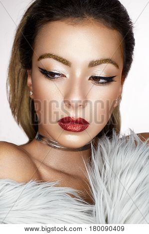 A young Asian girl with creative makeup, arrows and bright red lips with sparkles. A beautiful model with perfect skin in a fur coat made of artificial fur and a checker on neck. Beauty of the face.