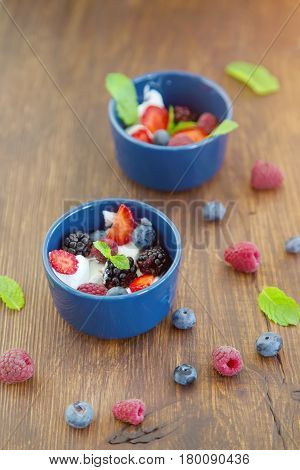 Milk fruit dessert. Whipped cream with berries. Serving tasty treats from dairy cream different berries and mint on the wooden table. Blue cup with cream berries and mint.