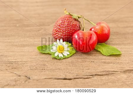 Ripe red strawberries cherries and small daisy flowers on a wooden background. Strawberries over wooden table background with copy spac