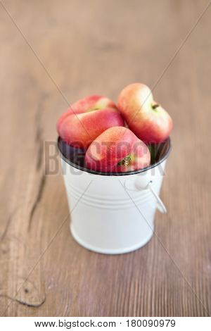 Fig peaches. Fresh flat peaches on wooden background. Fig peaches in white bucket. Selective focus.