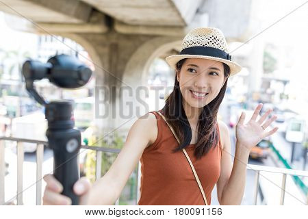 Woman using video stabilizer to take video at bangkok city