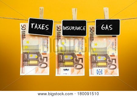 Bank Notes Suspended With Pins With Words - Taxe Insurance Gas - Written On A Slate