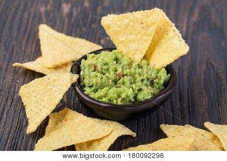 Corn chips nachos with sauce on a wooden table.