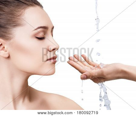 Beautiful woman face and splashes of water in hands. Cleansing and moisturizing concept.