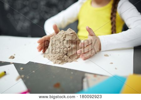 Hands of little girl around pile of kinetic sand