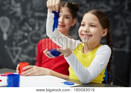 Smiling girl playing with blue slime in school