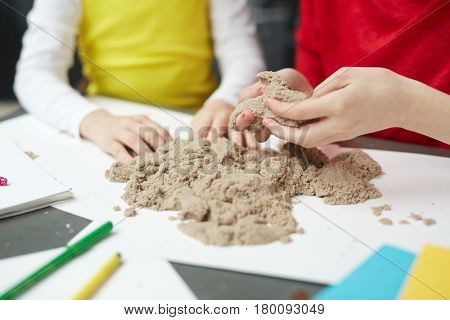 Kids playing with kinetic sand in elementary school