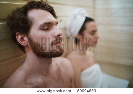 Peaceful man and his wife relaxing in sauna at leisure