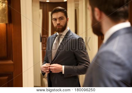View from back of a serious bearded man in suit looking at the mirror while being in a shop