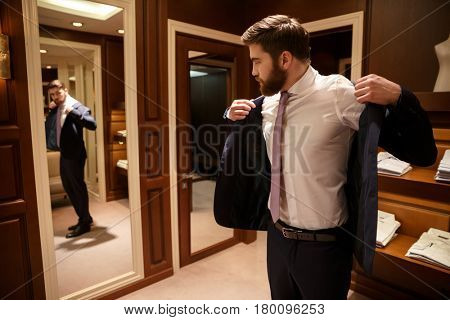 Bearded Man putting on his jacket while looking at the mirror