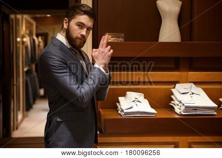 Side view of a bearded man in suit standing sideways and  showing gun sign while being in a shop and looking at the camera