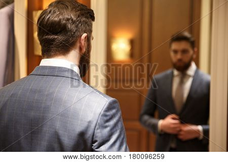View from back of bearded  man in suit looking at the mirror while being in a shop