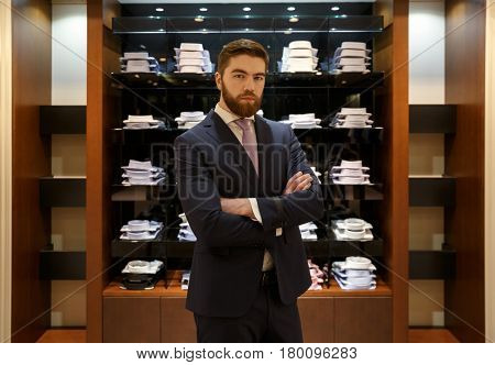 Man standing with crossed arms near the showcase in shop while looking at camera