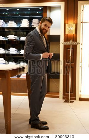 Vertical image of a Happy bearded man in suit which standing sideways in  shop and looking at camera