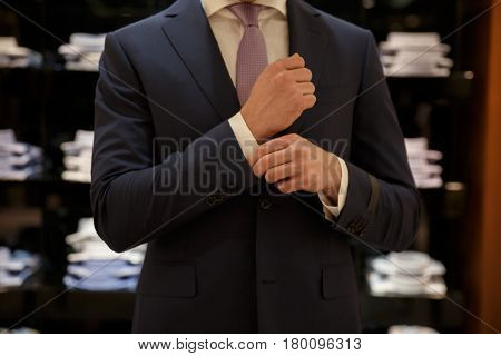 Cropped image of Man buttons up his shirt while standing near the showcase with shirts