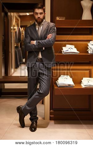 Vertical image of serious man in suit standing with crossed arms in shop while looking at camera. Full length portrait