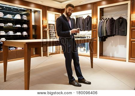 Full length portrait of happy man in suit standing in a shop and holding  smartphone while looking at the camera