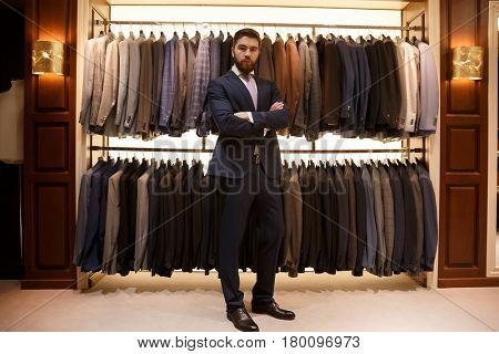 Full length portrait of bearded man in suit standing with crossed arms  near the rack with suits in a shop while looking at the camera