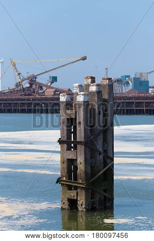 wooden poles that mark the waterway in front of a large steel plant