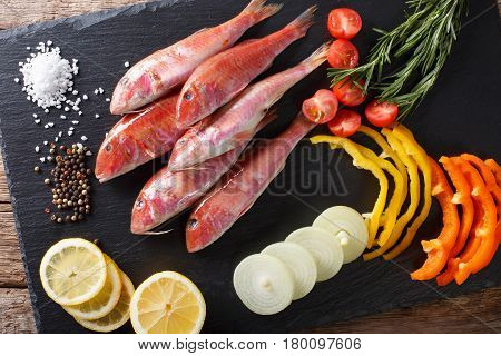 Raw Fish Red Mullet With Vegetables And Lemon Close-up On The Kitchen Board. Horizontal Top View
