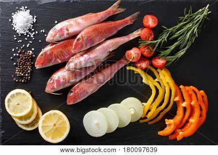 Raw Fish Red Mullet With Vegetables And Lemon On The Table. Horizontal Top View