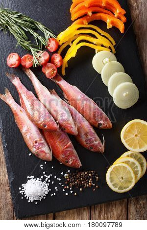Raw Fish Red Mullet With Vegetables And Lemon Close-up On The Kitchen Board. Vertical Top View