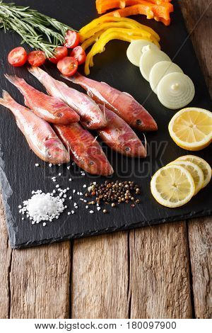 Raw Fish Red Mullet With Fresh Vegetables And Spices Close-up. Vertical