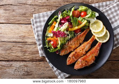 Roasted Red Mullet With Fresh Vegetables And Lemon Close-up. Horizontal Top View