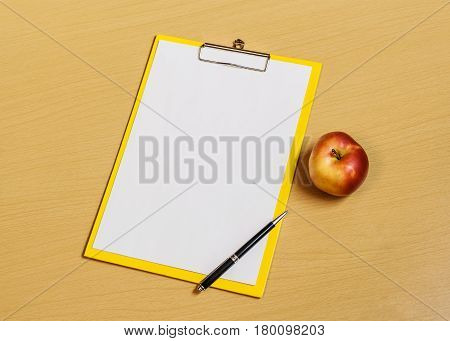 Clipboard with white sheet and pen on desk