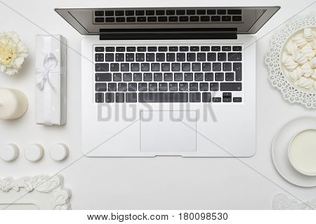 Overhead shot of a trendy feminine desktop with accessories arrangement in white color flat lay shot. Flat lay picture of a workspace of woman