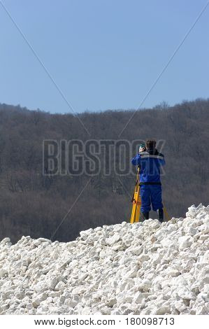 specialist surveyor in blue overalls makes measurements with a theodolite