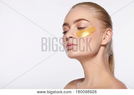 Beauty portrait of an attractive girl with a gold patch under the eye.