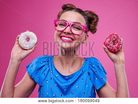 Close-up of happy woman showing two doughnuts isolated over pink background. Woman in pink glasses posing at the camera