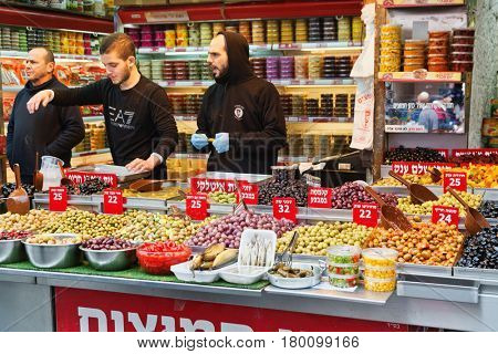 JERUSALEM, ISRAEL - DECEMBER 29, 2016: The sellers of pickled olives in the market of Mahane Yehuda in Jerusalem. More than 250 sellers sell fruits, vegetables, bakery, fish, meat , nuts and others