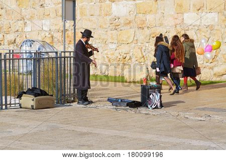 JERUSALEM, ISRAEL - DECEMBER 26, 2016:  A Jewish man in orthodox clothes plays the violin near the Jaffa gate to the old town of Jerusalem.