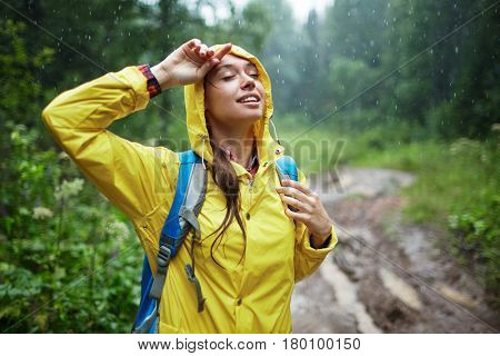 Young woman with backpack enjoying rainy weather