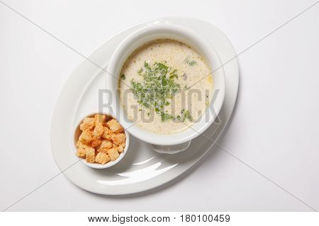 Delicious Creamy Soup With Croutons And Greens On White Dish