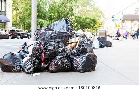 Pile of garbage bags on city street.