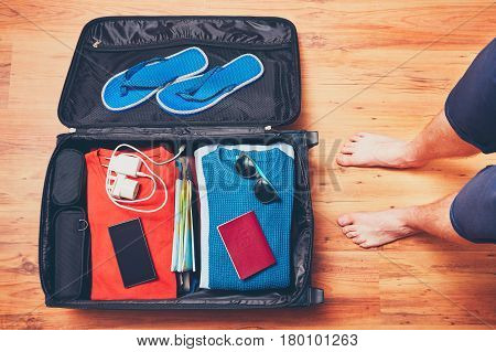 Preparing for the trip. Young man packing vacation items mobile phone and passport.