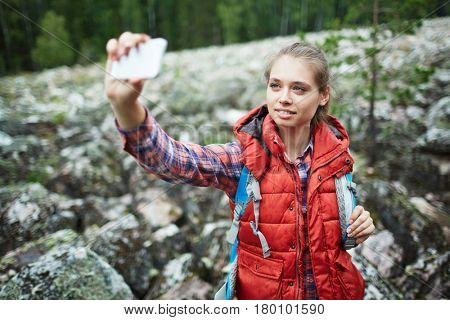 Pretty girl making selfie on background of big stones covered by moss during trip