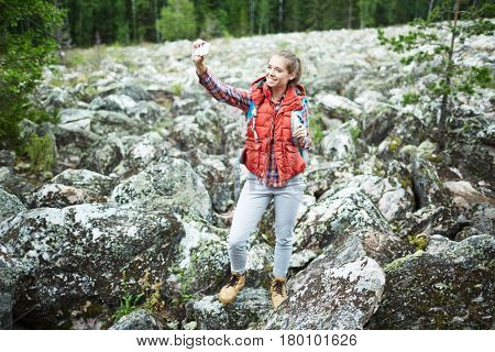 Young woman making her selfie during natural adventure
