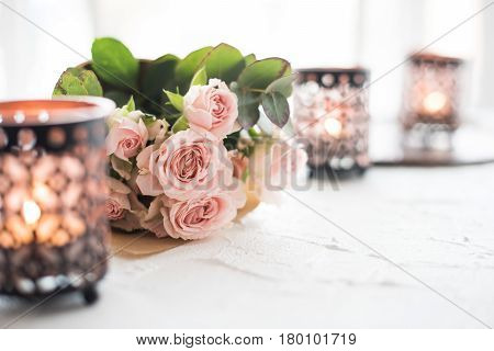 Beautiful bouquet of roses and candles in oriental candlesticks, elegant festive floral home decorations